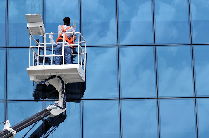 Window cleaner working on a glass facade in a gondola