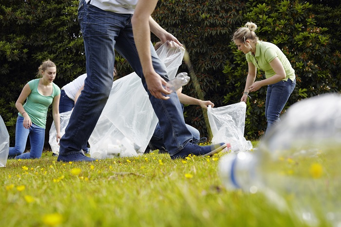 Volunteering: People cleaning up litter on grass